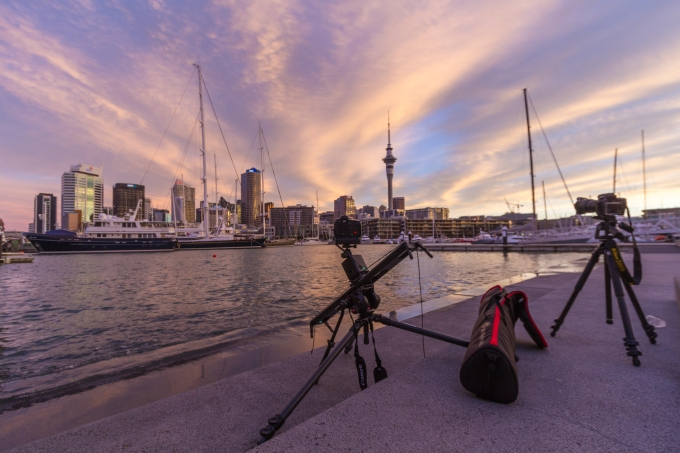 A time-lapse scene of sunset over Auckland CBD, super yachts and sailing boats in the harbour.
