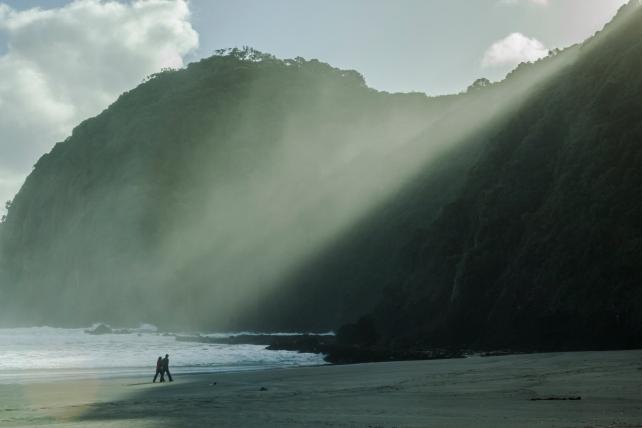 The sun cutting through sea mist at Piha