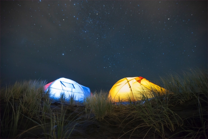 Glowing tents under a star sky