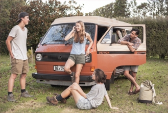 Backpackers posing with a classic VW camper van